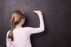 Blond chid girl kid writing on school chalkboard Royalty Free Stock Image
