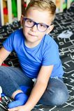Blond chil portrait. Little Child with reading glassses staying at home royalty free stock photo