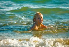 Blond child bathing in sea Stock Images