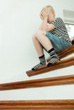 Blond child crying while seated on stairs Stock Photos
