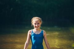 Blond child girl has fun in river. NChildhood in summer time. Happy Royalty Free Stock Photography