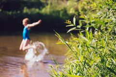 Blond child girl has fun in river. NChildhood in summer time. Happy Stock Photos