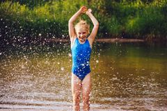 Blond child girl has fun in river stock photography