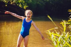 Blond child girl has fun in river. NChildhood in summer time. Happy! n Stock Image