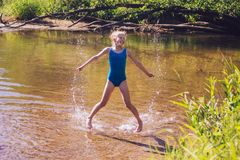 Blond child girl has fun in river. NChildhood in summer time. Happy Royalty Free Stock Photo