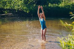 Blond child girl has fun in river. NChildhood in summer time. Happy Stock Photo