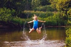 Blond child girl has fun in river. NChildhood in summer time. Happy Royalty Free Stock Photos