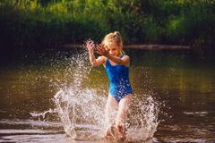 Blond child girl has fun in river. NChildhood in summer time. Happy Stock Image