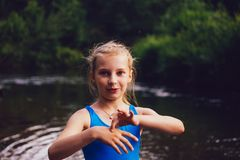 Blond child girl has fun in river. NChildhood in summer time. Happy! n Stock Photos