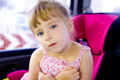 Blond child girl sitting in car safety seat Royalty Free Stock Photo