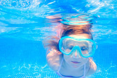 Blond child girl underwater swimming in pool. Blond child girl underwater swimming in blue tiles pool Royalty Free Stock Images