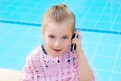 Blond child little girl talking mobile phone. Child little girl talking mobile phone in pool with happy gesture royalty free stock image