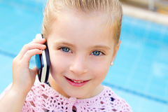 Blond child little girl talking mobile phone. Child little girl talking mobile phone in pool with happy gesture stock images