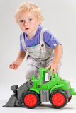 Blond child plays with tractor Royalty Free Stock Photo