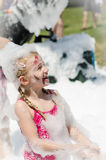 Blond child smiling at foam party Royalty Free Stock Image