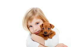 Blond children girl with dog puppy mini pinscher Royalty Free Stock Image
