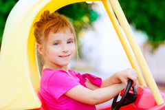 Blond children girl driving toy car. Yellow Royalty Free Stock Images
