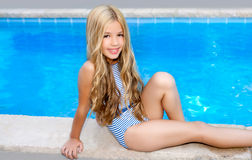 Blond children girl sittin in swimming pool border. In summer vacation Stock Images