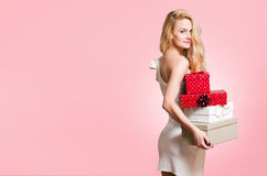 Blond christmas beauty. Portrait of a gorgeous young blond woman with Christmas gift boxes Royalty Free Stock Image
