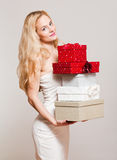 Blond christmas beauty. Portrait of a blond Christmas beauty holding gift boxes Stock Photography