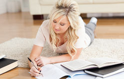 Blond College Student lying on the floor learning Royalty Free Stock Photos