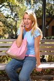 Blond college student on phone. Pretty blond college student answering cell phone while sitting on bench Royalty Free Stock Photo