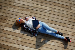 Blond in colorful glasses lying on the pier, and basking in the sun Stock Photos