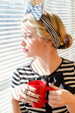 Blond contemplating beautiful young woman with red cup looking wistfully through window portrait Stock Photos