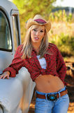 Blond country girl in hat and jeans. Tan blond country girl in red and white shirt tied in front, blue jeans and cowboy hat standing against old model pick up Royalty Free Stock Image