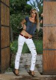 Blond cow girl in stable doors Royalty Free Stock Photo