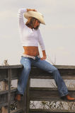 Blond cowgirl on fence in hat. Tan fit cowgirl in hat, white shirt, and blue jeans, sitting on wooden fence Stock Image