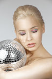 Blond with creative make up an shining ball. Portrait of blond young girl with a mirror shining ball aand some gem stone on eyes as a make up Stock Photography