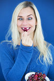 Blond cross-eyed woman eating a cherry. Portrait of a blond cross-eyed woman eating cherries with a blue background Stock Photo