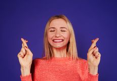 Blond with crossed fingers. Over violet background Royalty Free Stock Photos