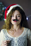 Blond curly beautiful smiling girl wearing Christmas hat holding fun paper mustache on Christmas decorations background Stock Photography