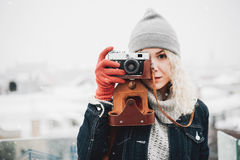 Blond curly girl with film photo camera, winter. Young blond curly female in warm clothes with retro film camera shooting a photo on the background of winter Stock Image