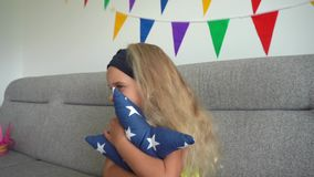 Curly hair girl hug star shape pillow and watch tv sit on sofa. Gimbal motion. Blond curly hair girl hug star shape pillow and watch tv sitting on sofa. Pretty stock video footage