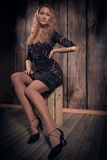 Blond curly hair lady sitting in a pose on the box over wooden wall background Royalty Free Stock Image