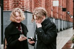 Blond curly-haired guy and the same girl are looking for information in mobile devices.  royalty free stock image