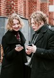 Blond curly-haired guy and the same girl are looking for information in mobile devices.  stock images