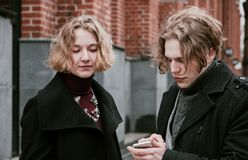 Blond curly-haired guy and the same girl are looking for information in mobile devices.  royalty free stock photography