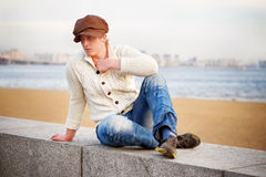 Blond curly man wearing knitting jacket and jeans sitting on the Royalty Free Stock Photos