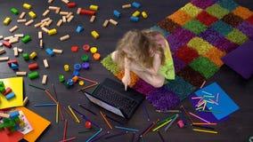 Blond curly preschool child watching cartoon on laptop, sitting on floor. Stock photo stock photography
