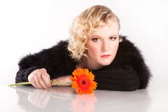 Blond curly woman with a flower. In her hands Stock Photo