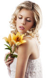 Blond curly woman holding lily Stock Photos