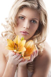 Blond curly woman holding lily Stock Image