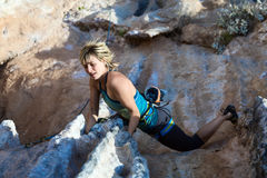 Blond Cute Climber on rocky terrain makes difficult move Stock Photo