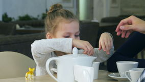 Blond cute girl tries to put sugar in her cup of tea. Her mother helps her. stock video footage