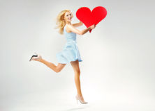 Blond cute lady running with heart Royalty Free Stock Image