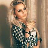 Blond dam för skönhet med exponeringsglas av martini som ser kameran Royaltyfri Foto
